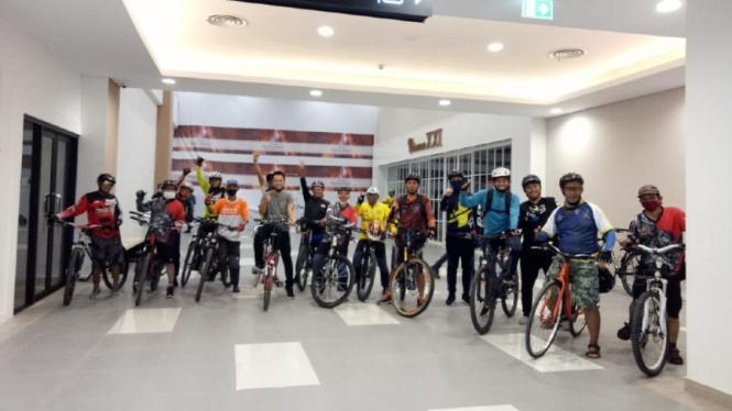 Komunitas pesepeda bersepeda di dalam mall.