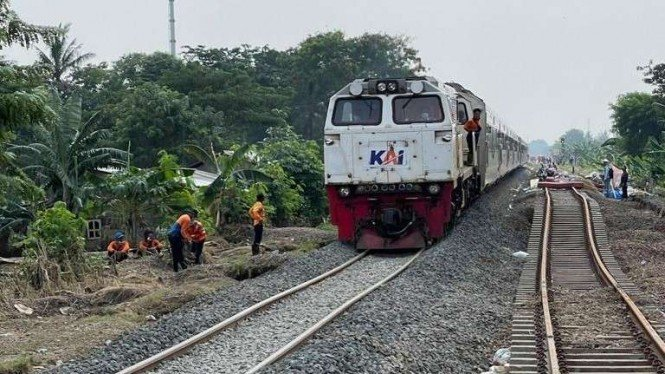 Uji coba rangkaian kereta api melintasi rel yang telah selesai diperbaiki akibat banjir.