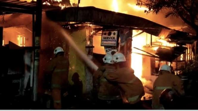 Regu pemadam kebakaran berusaha memadamkan api yang membakar sebuah rumah di Jalan Wonosari Kidul, Sawunggaling, Kecamatan Wonokromo, Kota Surabaya, Jawa Timur, pada Kamis malam, 25 Februari 2021.