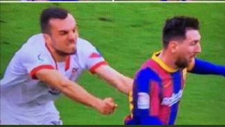 Gelandang Sevilla, Joan Jordan sedang berusaha menghentikan Lionel Messi.