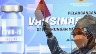 Tenaga kesehatan mengangkat bendera Merah Putih dalam pelaksanaan vaksinasi COVID-19 pada pegawai pemerintah di Jakarta, Kamis, 11 Maret 2021.