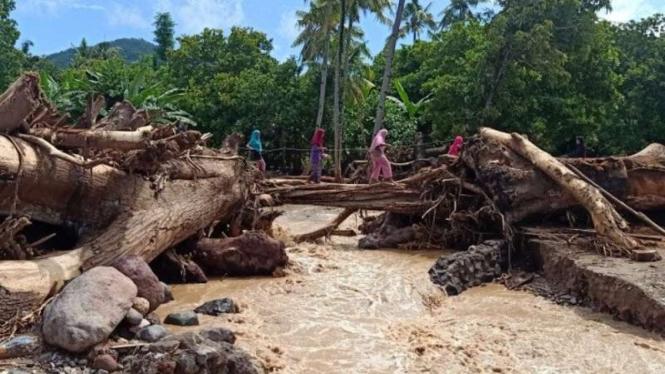 Warga Adonara Timur melintasi tumpukan kayu yang terbawa arus dari Bukit Air Areng di Kali Mati yang membelah Desa Waiburak dan Desa Waiwerang di Kecamatan Adonara Timur, Kabupaten Flores Timur, NTT, Rabu, 7 April 2021.