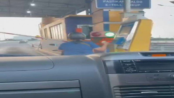 Seorang ibu masuk dalam tol dengan sepeda motor