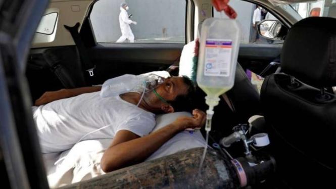 Seorang pasien dengan gangguan pernapasan berbaring di dalam mobil sambil menunggu untuk masuk rumah sakit COVID-19 untuk perawatan, di tengah penyebaran COVID-19 di Ahmedabad, India, Kamis 22 April 2021.