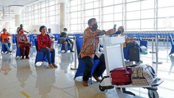 Penumpang pesawat antre dengan berjarak di Bandara Internasional Yogyakarta