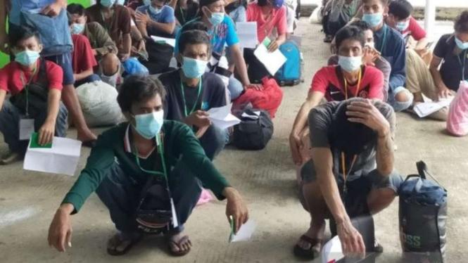 Sejumlah pekerja migran Indonesia yang dideportasi dari Malaysia tiba di Pelabuhan Tunon Taka, Nunukan, Kalimantan Utara, menunggu giliran untuk pemeriksaan swab oleh Satgas Penanganan COVID-19 pada 22-23 April 2021.