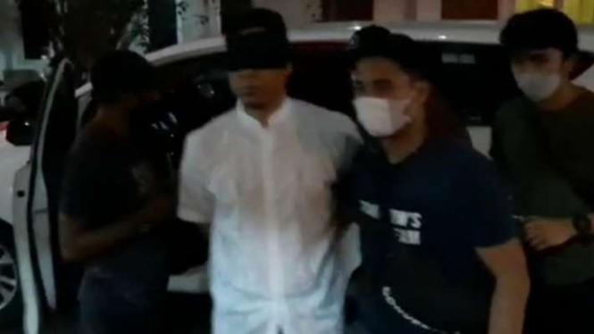 Munarman tiba di Polda Metro Jaya dengan mata ditutup.