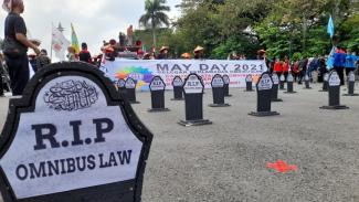 Batu nisan bertuliskan RIP Omnibus Law dalam aksi hari buruh di kawasan Monas.
