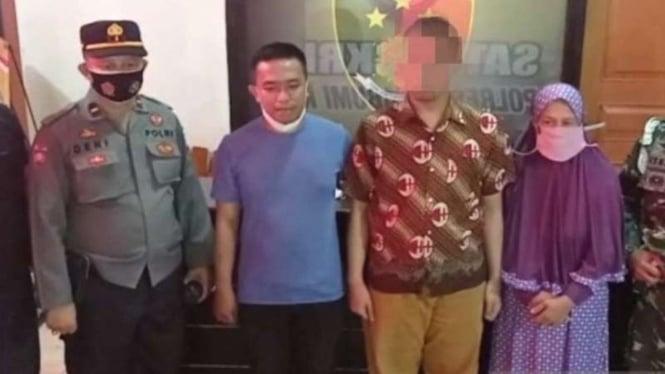 """Seorang pria berinisial HH pemilik akun Facebook """"Kholip Ajaw"""" (menggunakan kemeja batik), terduga penghina TNI dan kru kapal selam KRI Nanggala-402, didampingi keluarganya di markas Polres Sukabumi, Sabtu, 1 Mei 2021."""
