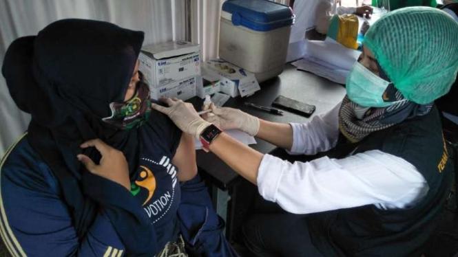 Seorang petugas kesehatan menyuntikkan vaksin COVID-19.