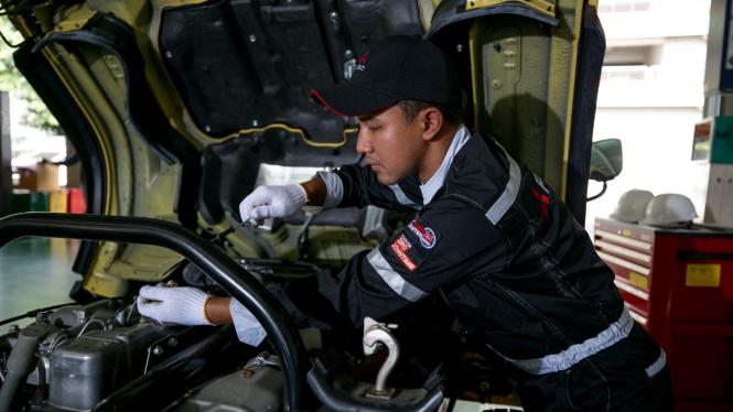 Mekanik memperbaiki truk Fuso
