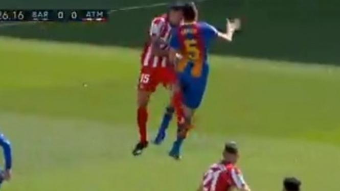 Sergio Busquets berbenturan dengan Stefan Savic saat duel udara.