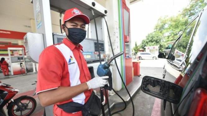 Petugas sedang melakukan pengisian bahan bakar.