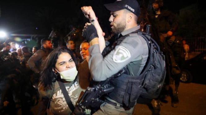 Wanita Palestina bentrok dengan polisi Israel selama protes terhadap rencana penggusuran keluarga Palestina di lingkungan Sheikh Jarrah [Mahmoud Illean / AP]