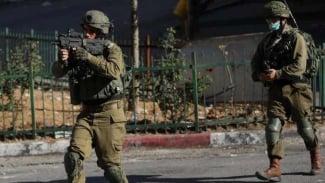 Tentara Israel membidikkan senapannya ke arah demonstran Palestina.