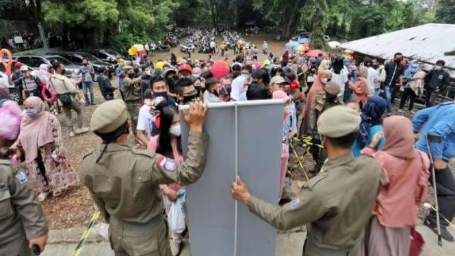 Aparat Satpol PP menertibkan para warga pengunjung Kebun Binatang Kota Bandung untuk disiplin menerapkan protokol kesehatan pencegahan COVID-19 dalam satu operasi razia, Minggu, 16 Mei 2021.