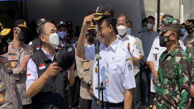 Gubernur DKI Jakarta Anies Baswedan bertukar topi dinas dengan pak RW di Sunter