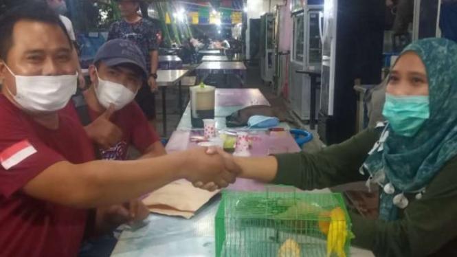 Didik Saputra (kiri), pria asal Kabupaten Lamongan, Jawa Timur, bertransaksi barter menukar satu mobil Honda CR-V tahun 2009 dengan sepasang burung love bird YF milik seorang wanita di Surabaya, Jumat malam, 28 Mei 2021.