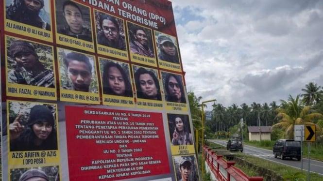 Sejumlah pengendara mobil melintas di depan baliho yang menampilkan buronan anggota Mujahidin Indonesia Timur (MIT) Poso di Desa Tambarana, Poso Pesisir Utara, Kabupaten Poso, Sulawesi Tengah, Rabu, 23 Desember 2020.