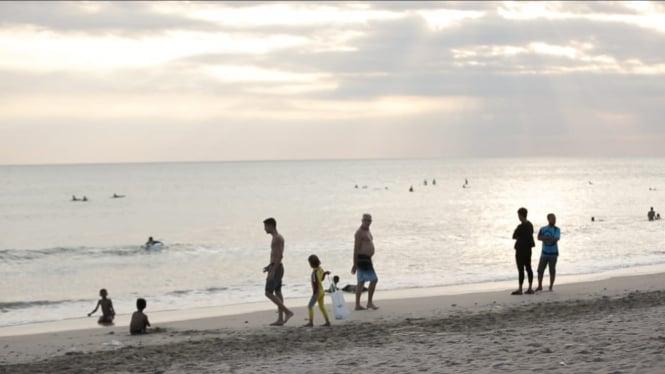 wisatawan sedang bermain di pantai Kuta Bali.