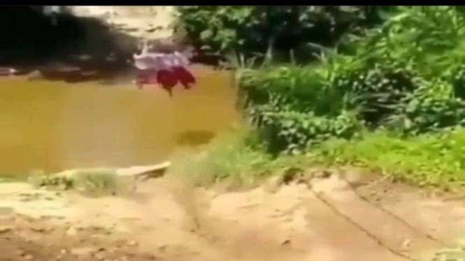 Tangkapan layar pelajar menyebrangi sungai untuk bersekolah