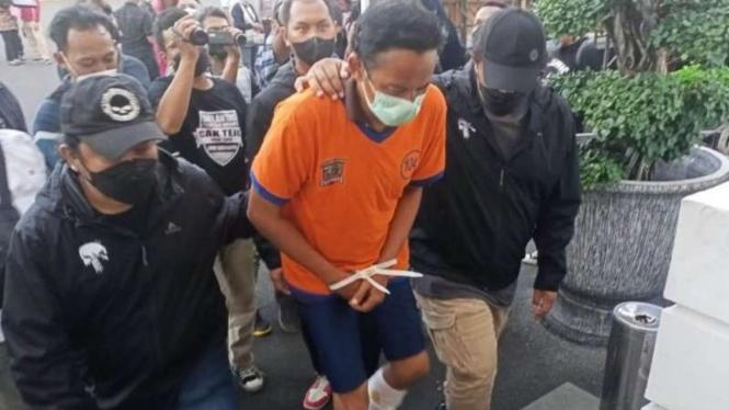 Polisi memperlihatkan seorang pria yang disangka menganiaya bocah hingga tewas beberapa saat setelah ditangkap dalam konferensi pers di Markas Polres Kota Besar Surabaya, Jumat, 11 Juni 2021.