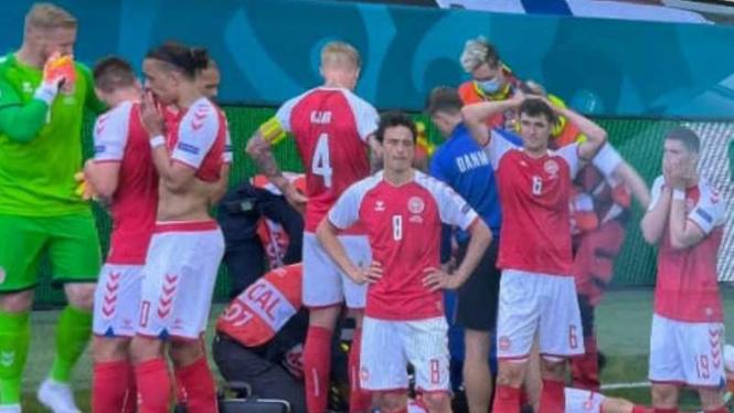 Timnas Denmark menutupi Christian Eriksen yang sedang ditangani tim medis.