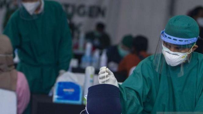 Petugas mengambil sampel lendir hidung untuk pemeriksaan tes cepat antigen COVID-19 pemudik secara gratis di Unit Pelaksana Pengujian Kendaraan Bermotor (UPPKB) Balonggandu, Karawang, Jawa Barat, Minggu, 16 Mei 2021.