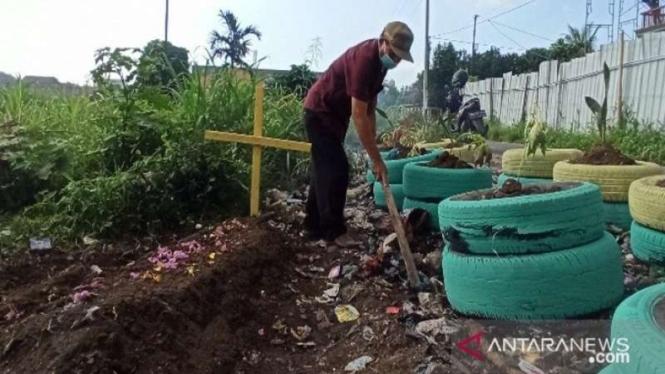 Petugas lingkungan membuat replika kuburan di tepi jalanan yang banyak sampah