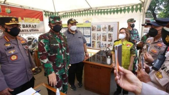 Sejumlah anggota Polri memperlihatkan buku panduan pedoman kontinjensi klaster COVID-19 kepada Kepala Polri Jenderal Polisi Listyo Sigit Prabowo saat mengunjungi lokasi PPKM Mikro di Semper Barat, Jakarta Utara, Minggu, 27 Juni 2021.