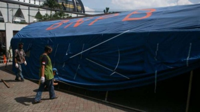 Relawan membangun tenda barak di Rumah Sakit Umum Pusat Dr. Sardjito, Sleman, DI Yogyakarta, Minggu, 27 Juni 2021, untuk mengantisipasi membludaknya pasien COVID-19 seiring lonjakan kasus penularan.