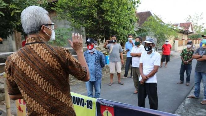 Gubernur Jawa Tengah Ganjar Pranowo (kiri) saat meninjau PPKM mikro yang dikelola dengan metode Jogo Tonggo di Desa Wirun, Kecamatan Kutoarjo, Kabupaten Purworejo, Kamis, 1 Juli 2021.