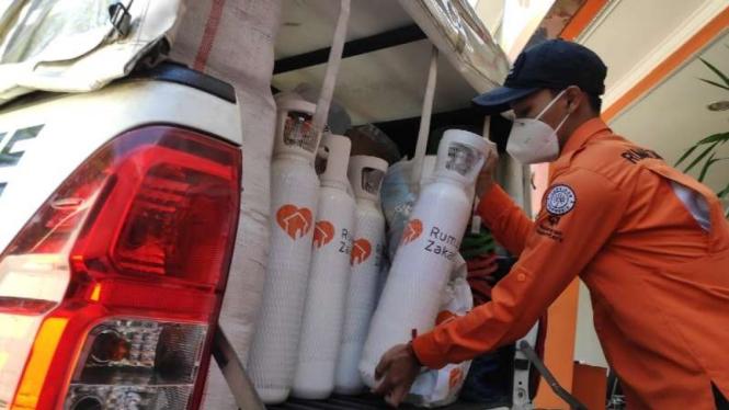 Seorang petugas lembaga pengelola zakat dan infak, Rumah Zakat, memasukkan sejumlah tabung oksigen medis untuk didistribusikan ke beberapa rumah sakit rujukan pasien COVID-19 menyusul kelangkaan produk itu di pasaran.