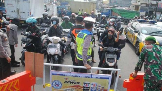 Petugas gabungan menutup jalan saat penyekatan kendaraan di Bogor.