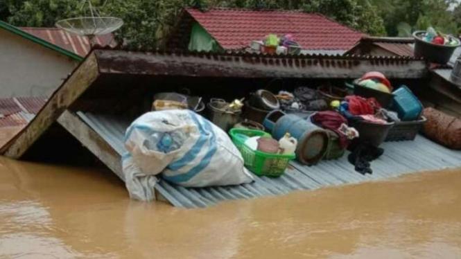 Atap rumah seorang warga di Kabupaten Kapuas Hulu, Provinsi Kalimantan Barat, dijadikan tempat untuk menyimpan sejumlah barang menyusul banjir setinggi loteng yang merendam daerah itu, Kamis, 15 Juli 2021.