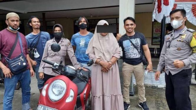 Polisi memperlihatkan seorang perempuan berkerudung, residivis pencurian, yang berhasil ditangkap setelah aksi kejar-kejaran dengan sepeda motor di jalan raya di Kota Banjarbaru, Kalimantan Selatan, Kamis, 15 Juli 2021.