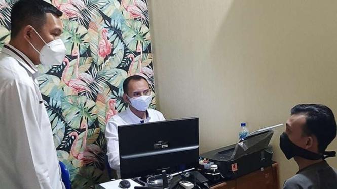Pengunggah selebaran ajakan demo memprotes PPKM Darurat, NP, saat diperiksa oleh Kepala Satuan Reserse Kriminal Polresta Banyumas Komisaris Polisi Berry (kiri) di kantor Polresta Banyumas, Senin, 19 Juli 2021.