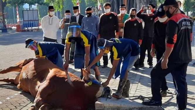 Tiga orang petugas dengan mengenakan masker dan pelindung wajah sesuai protokol kesehatan pencegahan COVID-19 menyembelih sapi kurban dalam momen hari raya Idul Adha di Kota Solo, Jawa Tengah.