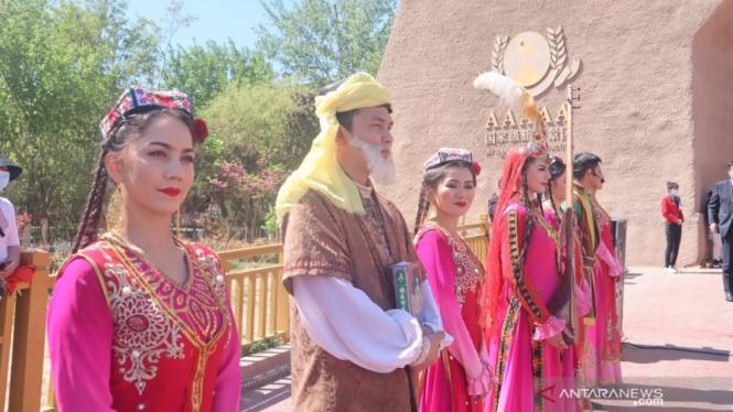 Perempuan etnis minoritas Muslim Uighur menyambut para wsiatawan di gerbang Kota Tua Kashgar, wilayah selatan Daerah Otonomi Xinjiang, China.