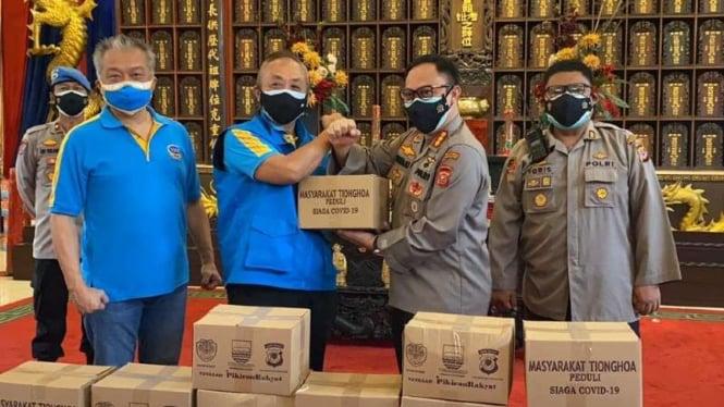 Koordinator Pemuda Pemudi Masyarakat Tionghoa Peduli, Hendry Bunardi, menyerahkan secara simbolik kepada polisi bantuan paket sembako untuk para pedagang kecil yang terdampak PPKM Darurat di Bandung, Kamis, 22 Juli 2021.