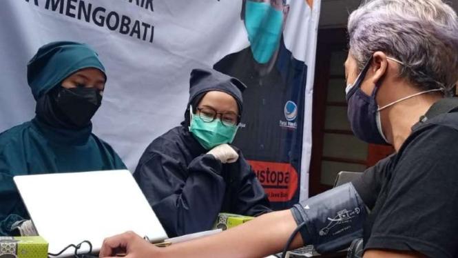 Dua petugas medis melayani seorang warga yang hendak disuntik vaksin COVID-19 dalam kegiatan vaksinasi secara massal di kantor Partai Nasdem Jawa Barat di Bandung, Kamis, 22 Juli 2021.