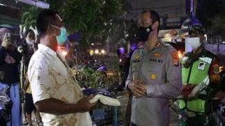 Kapolres Pelabuhan Tanjung Priok AKBP Putu Kholis memberikan bansos ke warga