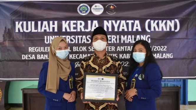 Perwakilan peserta KKN UM bersama perwakilan perangkat desa dalam simbolis penyerahan Administrasi dan Controlling Berbasis Website