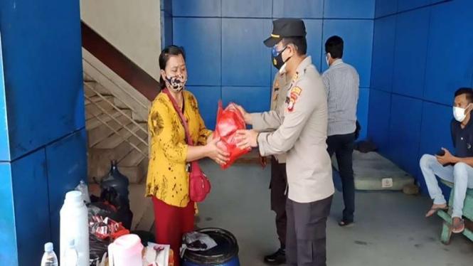 Polisi memberikan bantuan sosial (bansos) bagi warga terdampak PPKM