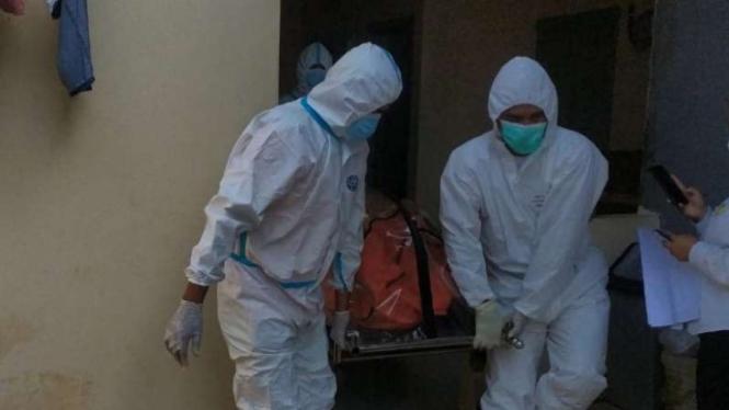 Tim Satgas COVID-19 mengevakuasi jenazah seorang pria yang ditengarai terjangkit virus corona dan meninggal dunia saat isolasi mandiri di satu kamar indekos di Kota Bekasi, Jawa Barat, Senin, 26 Juli 2021.