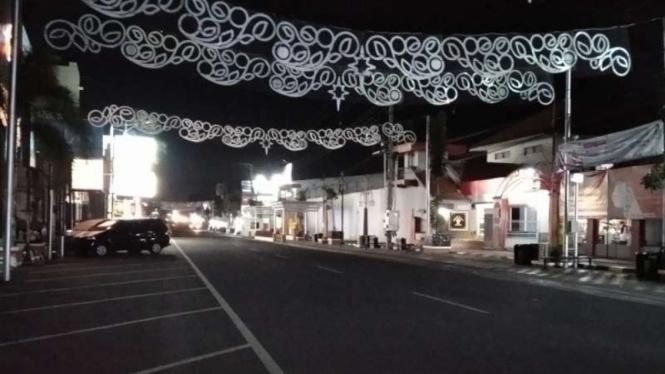 Jalan Sunan Kudus, Jawa Tengah, pada malam hari tampak tidak ramai pedagang kaki lima (PKL) karena banyak yang tidak berjualan selama penerapan pemberlakuan pembatasan kegiatan masyarakat (PPKM).