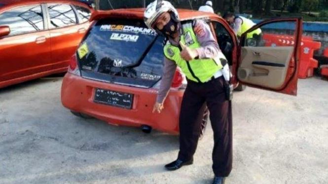 Polisi menilang mobil yang menggunakan knalpot bising.