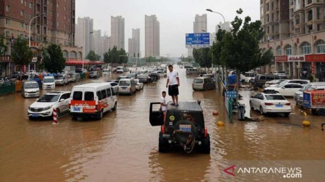 Warga berada di atas mobilnya saat banjir yang merendam jalanan di Henan, China