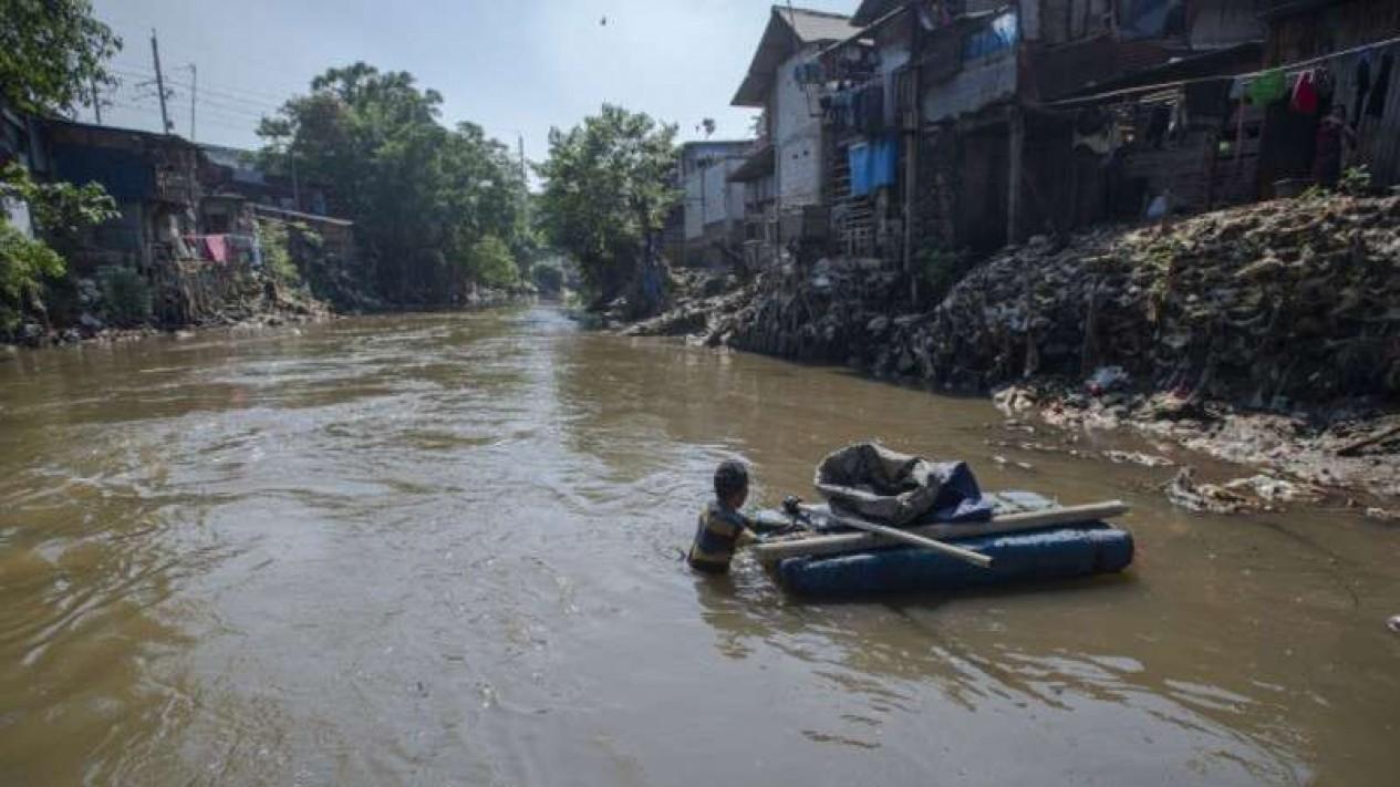 Warga mengambil sampah yang hanyut di sungai Ciliwung