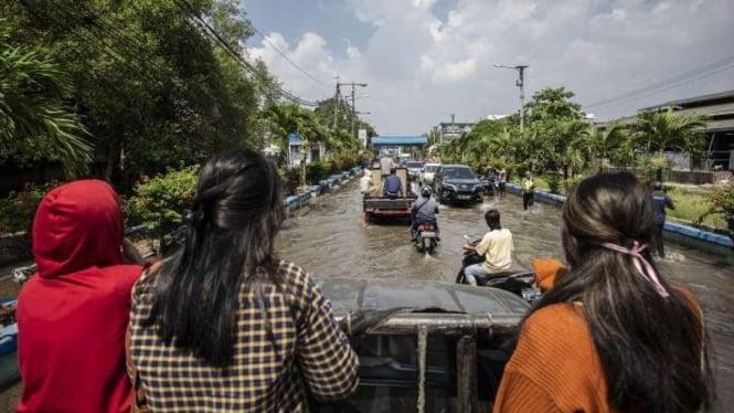 Warga menumpang mobil bak saat melintasi banjir rob di Muara Baru.